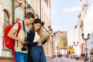 Young man and girl as two tourists with city map