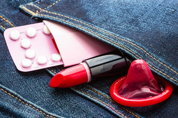 Pills condom and lipstick in denim pocket.