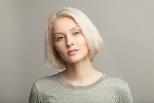 close up portrait of young beautiful blonde woman on gray background