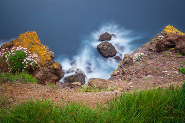 Long exposure image of rock island with a few white birds of gull in ocean, Bretagne, France.