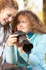 Two girls look through pictures on camera