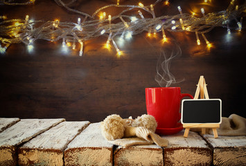 Cup of hot coffee and blackboard on wooden table in front of snowy garland lights background
