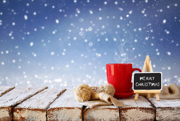 """Cup of hot coffee and cozy knitted scarf and blackboard with words """"merry christmas"""" written on it, on wooden table in front of glitter snowy background"""