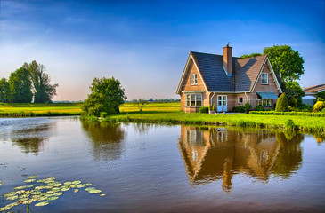 Red bricks house in countryside near the lake with mirror reflec