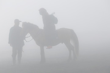 Silhouette of two person and horse in fog and smoke of volcano Bromo
