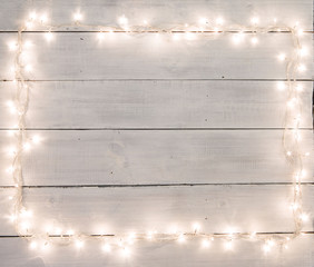Christmas lights on white painted wooden background with copy sp