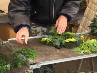 fiorista che crea una ghirlanda natalizia