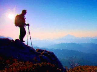 Watercolor paint. Paint effect. Tourist with sporty backpack and poles in hands stand on rocky view point and watching into deep misty valley bellow. Sunny spring daybreak