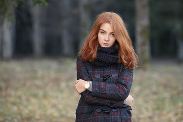 Outdoors portrait of young beautiful redhead woman in scarf and jacket on forest blurred background
