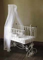 Baby bed. Antique furniture from 19th century.
