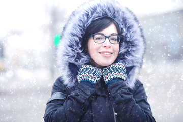 snowy winter portrait of a girl in the city on the road