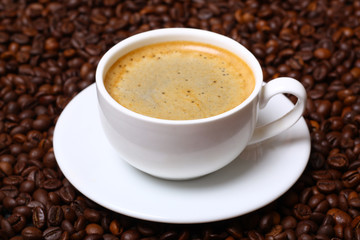 Cup of hot coffee and coffee beans closeup
