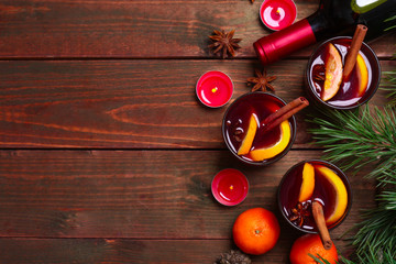 Christmas mulled wine in glasses with orange on wooden table, close up
