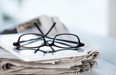 Stack of newspapers, eyeglasses and digital tablet