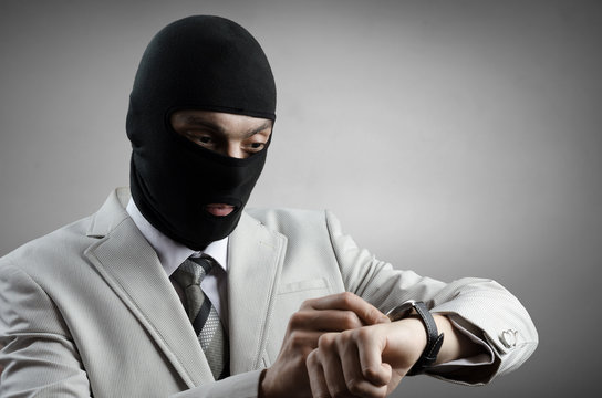 robber in a white tuxedo looks at the clock