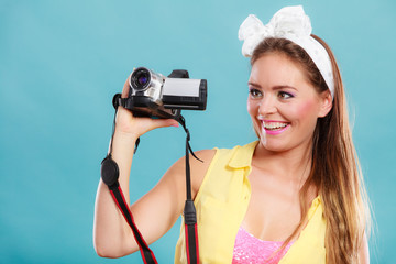 Happy pin up girl woman filming with camcorder.