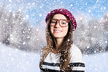 Happy attractive girl in hipster glasses on snowy winter background