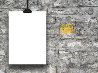 Single hanged paper sheet frame with clip on grey historical stone wall background