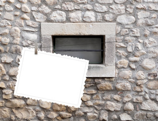 One hanged postcard with peg on old stone wall background with small window
