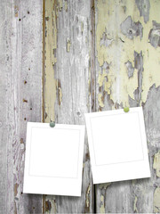 Double square empty photo frames with pins on scratched grey wooden boards background