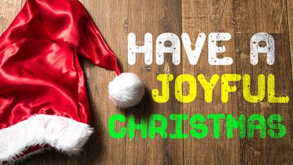Have a Joyful Christmas written on wooden with Santa Hat