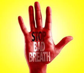 Stop Bad Breath written on hand with yellow background
