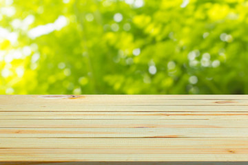 Close up top wooden table with sunny abstract green nature background, blurred bokeh