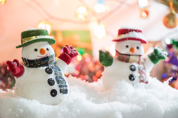 Snowman stand among pile of snow at silent night with a light bulb, light up the hopefulness and happiness in Merry christmas and new year night.
