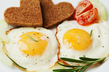 Aluminium Prints Egg Fried eggs with fresh vegetables and toast in shape of heart on white plate, delicious Breakfast