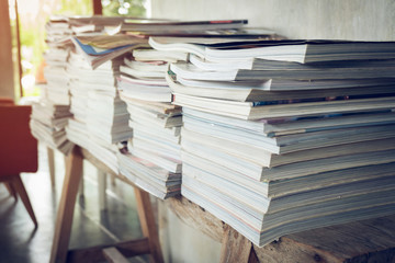 stack of magazine book on wooden table shelf in living room