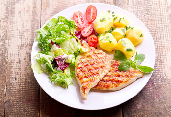 plate of grilled chicken breast with vegetables