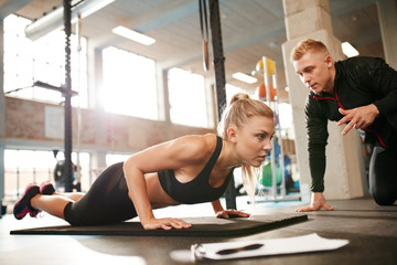 Female exercising with personal trainer at gym