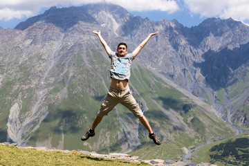 Young man jumping with hands up against the sky and mountain