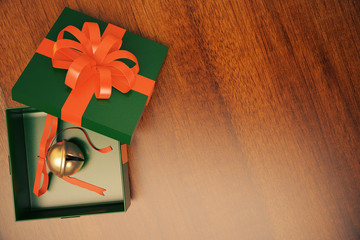 Green gift box with jingle bell inside on wooden floor