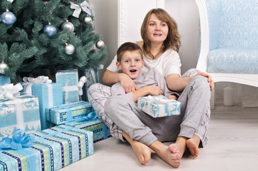 Cheerful mother and son in pajamas near Christmas tree with pres
