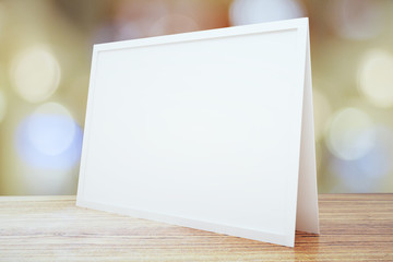 Blank picture frame on wooden table, mock up