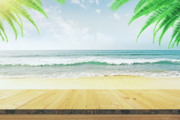 Empty wooden table on the beach with palm trees