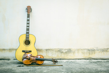 Acoustic guitar with violin vintage style old wall background