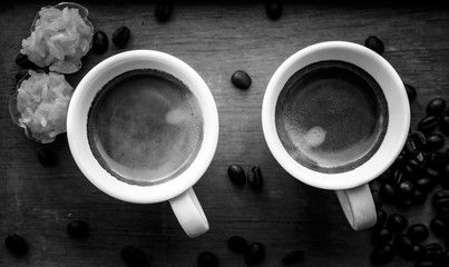 Two espresso coffees in small white cups,with a coffee bean rest