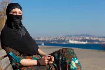 Muslim Style dressed Lady sitting on wooden Bench Pensive