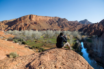 Photographer taking a landscape photo of gorgeous Dades Gorge valley, Morocco