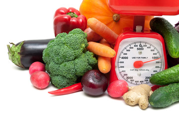 kitchen scale and vegetables on a white background