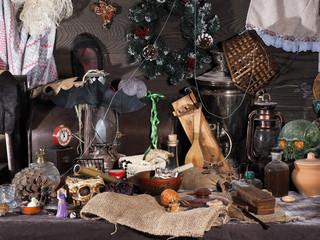 На старом пыльном чердаке. Множество разных старых предметов - часы будильник, керосиновые лампы, самовар, сломанные игрушки, коробки и шкатулки, черепа, нитки. Новогодний венок и старые туфли.