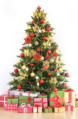 Beautifully decorated Christmas tree with many presents at home