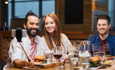 friends taking selfie by smartphone at restaurant
