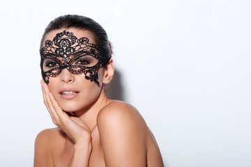 Woman with evening smokey makeup and black lace mask
