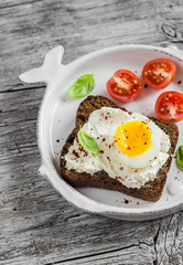 Sandwich with feta cheese and boiled egg, tomatoes, and basil on a white plate on a wooden surface. Healthy breakfast or snack