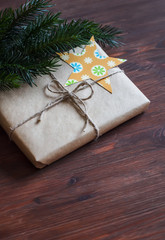 Homemade Christmas gifts in kraft paper with handmade tags and a Christmas tree on dark brown wooden surface. Vintage and rustic style