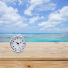 Clock on wood table top with sea background
