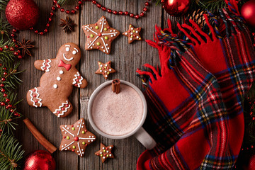 Cup of hot chocolate or cocoa with gingerbread cookies and warm scarf composition in fur tree decorations frame on vintage wooden table background. Homemade traditional food recipe